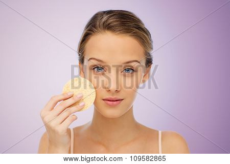 beauty, people and skincare concept - young woman cleaning face with exfoliating sponge over violet background