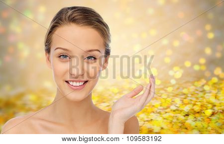 beauty, people and health concept - smiling young woman face and shoulders over golden glitter or holidays lights background