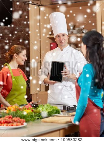 cooking class, culinary, food, technology and people concept - happy women with chef cook showing blank tablet pc screen in kitchen over snow effect