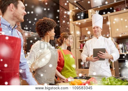 cooking class, culinary, food, technology and people concept - happy friends with tablet pc in kitchen over snow effect