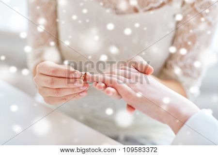 people, homosexuality, same-sex marriage and love concept - close up of happy lesbian couple hands putting on wedding ring over snow effect