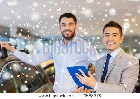auto business, car sale, technology and people concept - happy man and car dealer with tablet pc computer in auto show or salon over snow effect