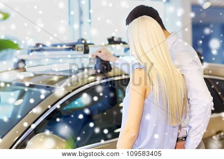 auto business, car sale, consumerism and people concept - couple choosing car in auto show or salon over snow effect from back