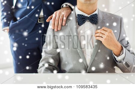 people, celebration, homosexuality, same-sex marriage and love concept - close up of male gay couple with wedding rings on putting hand on shoulder over snow effect
