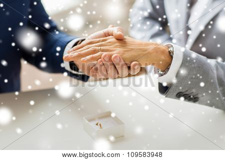 people, homosexuality, same-sex marriage and love concept - close up of happy male gay couple hands with wedding ring on and little box on table over snow effect
