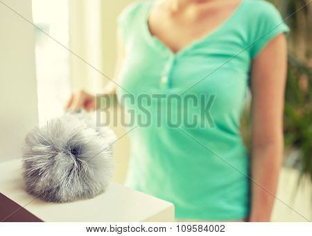 people, housework and housekeeping concept - close up of happy woman with duster cleaning at home