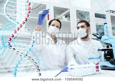 science, chemistry, technology, biology and people concept - young scientists with test tube and microscope making research in clinical laboratory over dna molecule structure