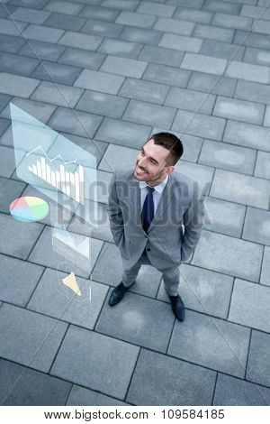business, development and people concept - young smiling businessman with growth chart outdoors from top