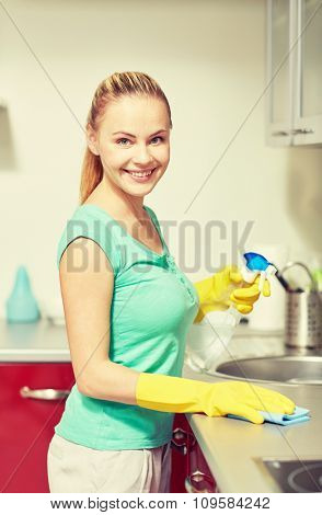 people, housework and housekeeping concept - happy woman in protective gloves cleaning table with rag and cleanser at home kitchen