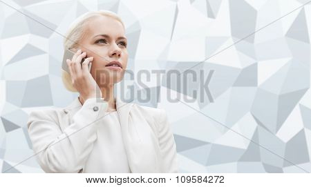 business, technology and people concept - serious businesswoman with smartphone talking over gray graphic low poly background
