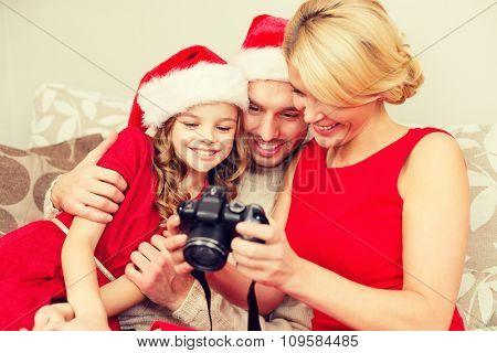 family, christmas, x-mas, happiness and people concept - smiling family in santa helper hats looking at pictures