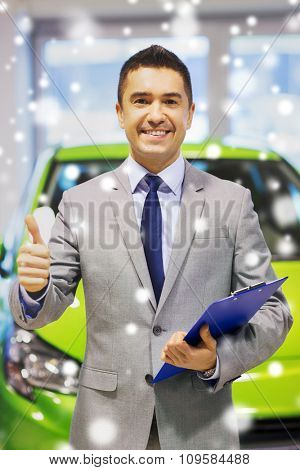 auto business, car sale, consumerism, gesture and people concept - happy man showing thumbs up at auto show or salon over snow effect