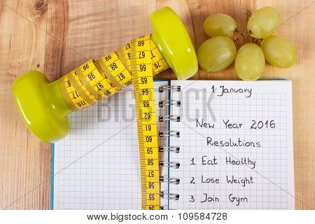 New Years Resolutions Written In Notebook And Dumbbells With Centimeter