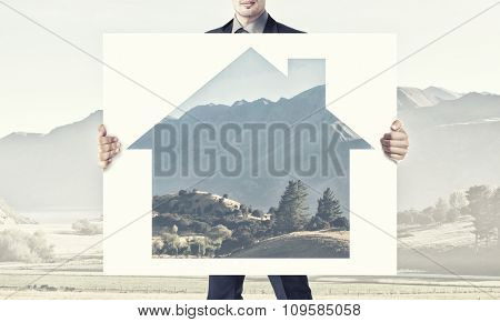 Businessman in suit holding placard with house symbol