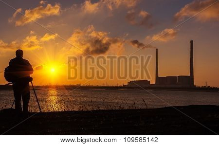Photographer At Sunrise On The Coast, On A Background Of Pipes Power