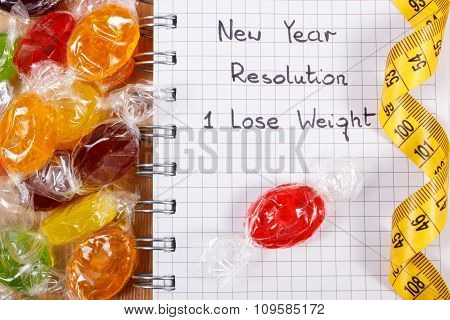 New Years Resolutions Written In Notebook, Candies And Tape Measure