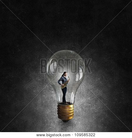 Young woman in suit with saxophone in hands inside glass light bulb