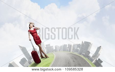 Young woman in red dress with red luggage talking on mobile phone