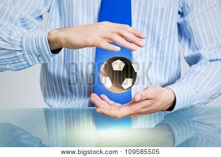 Hands of businessman holding with care soccer ball