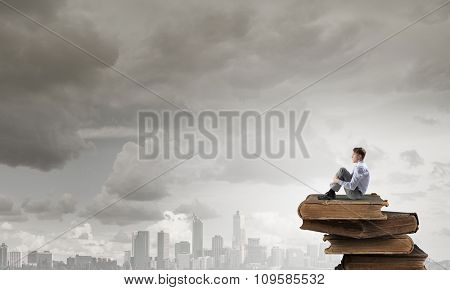Young businessman sitting alone on pile of old books