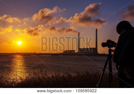 Photographer Silhouette At Sunrise On The Background Of The Plant