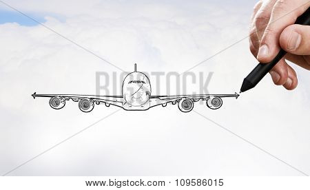 Person drawing airplane model on sky background