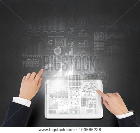 Businessman analyzing financial statistics displayed on tablet screen