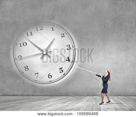 Woman in Santa hat pulling clock with rope