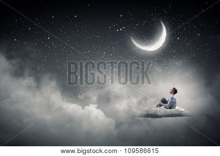 Businessman in suit sitting on cloud in isolation and looking at moon
