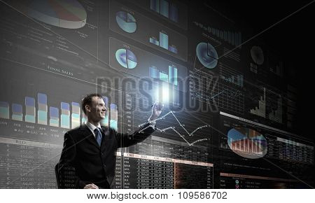 Rear view of businessman drawing with marker infographs on wall