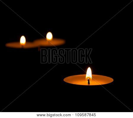 Three Burning Candles With Reflection On Black Background