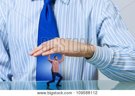 Young man under pressure of human big hand
