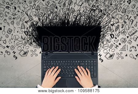 Top view of businesswoman hands using black laptop