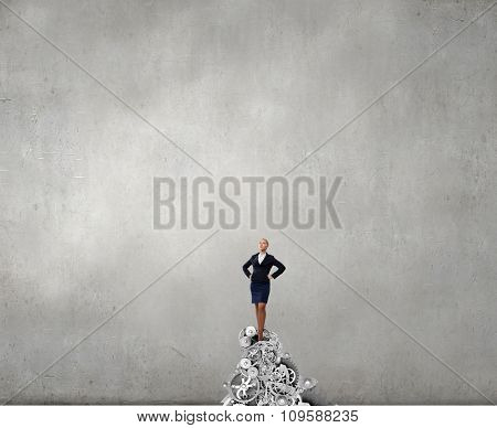 Confident businesswoman standing on top of gears