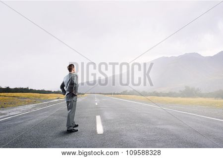Young businessman with arms on waist standing on asphalt road