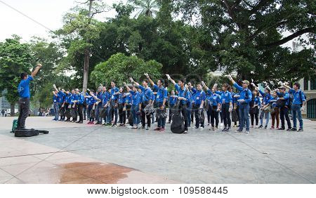 Asian students warming up before go to clean the bank of Hoan Kiem lake