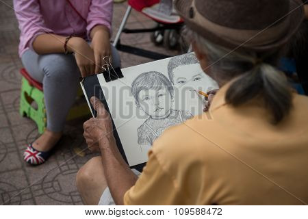 Asian portrait painter drawing image of customer by pencil