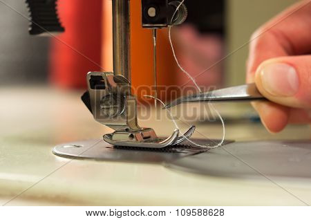 Hand With Tweezers Gives The Thread The Needle Of The Sewing Machine