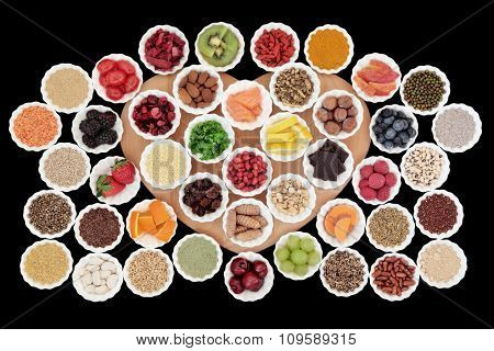 Health and diet superfood food selection in porcelain crinkle bowls on a heart shaped board over black background. High in vitamins and antioxidants.