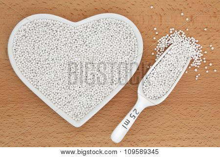 Tapioca pearls in a heart shaped porcelain dish and scoop over beech wood background.