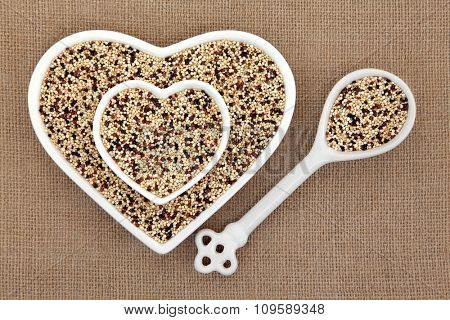 Tricolour quinoa grain super food in heart shaped bowls and porcelain spoon over hessian background.