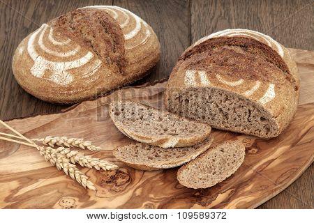 Crusty fresh homemade rye bread on an olive wood board with wheat sheaths over oak background.