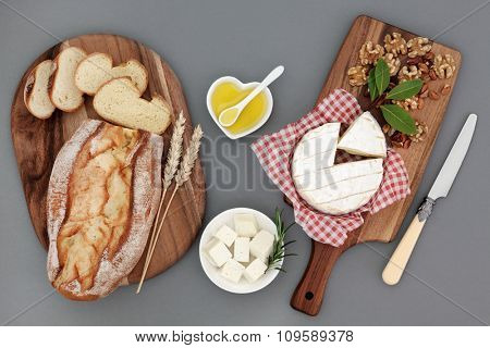 Healthy cheese snack with feta and camembert, olive oil, herbs, walnut and pistachio nuts, with fresh bread loaf and wheat sheaths on maple boards.