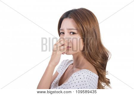 Portrait of a young woman holding her nose because of a bad smell.