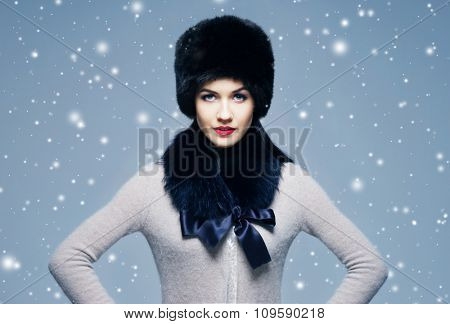 Portrait of a young and beautiful lady in a typical Russian winter clothes over background with snowflakes.