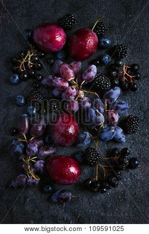 Fresh Dark Fruits And Berries On Black Background.