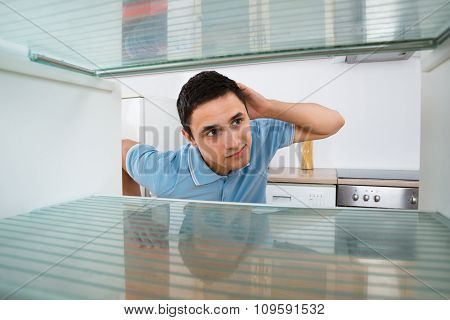 Shocked Man Looking Into Empty Refrigerator