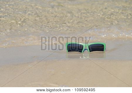 Green Sunglass On The Wet Sand And Wave On Background