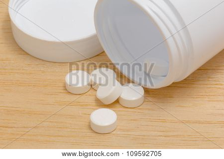 Pills Spilling Out Of Pill Bottle On Wood Back Ground