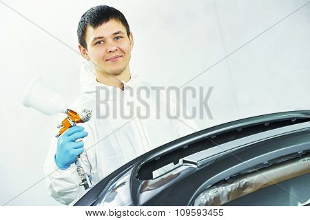portrait of automobile repairman painter in protective workwear with spray gun in his hand